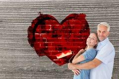Σύνθετη εικόνα του ευτυχούς ζεύγους που αγκαλιάζει και που κρατά τον κύλινδρο χρωμάτων Στοκ Εικόνες