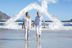 Σύνθετη εικόνα του ευτυχούς ζεύγους που περπατά χωρίς παπούτσια στην παραλία Στοκ εικόνες με δικαίωμα ελεύθερης χρήσης