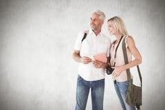 Σύνθετη εικόνα του ευτυχούς ζεύγους τουριστών που χρησιμοποιεί τον τουριστικό οδηγό Στοκ εικόνα με δικαίωμα ελεύθερης χρήσης