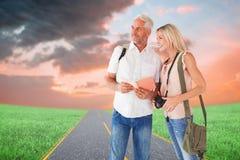 Σύνθετη εικόνα του ευτυχούς ζεύγους τουριστών που χρησιμοποιεί τον τουριστικό οδηγό Στοκ Φωτογραφία
