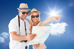 Σύνθετη εικόνα του ευτυχούς ζεύγους τουριστών που χρησιμοποιεί το χάρτη και την υπόδειξη Στοκ φωτογραφίες με δικαίωμα ελεύθερης χρήσης