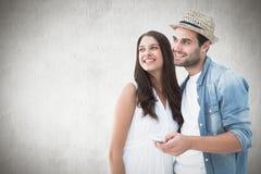 Σύνθετη εικόνα του ευτυχούς ζεύγους hipster που χαμογελά από κοινού Στοκ εικόνα με δικαίωμα ελεύθερης χρήσης