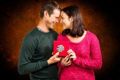 Σύνθετη εικόνα του ευτυχούς κιβωτίου δώρων εκμετάλλευσης ζευγών Στοκ Φωτογραφίες