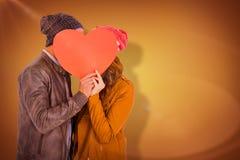 Σύνθετη εικόνα του ευτυχούς νέου εγγράφου μορφής καρδιών εκμετάλλευσης ζευγών Στοκ Εικόνες