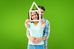 Σύνθετη εικόνα του ευτυχούς νέου ζεύγους με τη μορφή σπιτιών Στοκ φωτογραφία με δικαίωμα ελεύθερης χρήσης