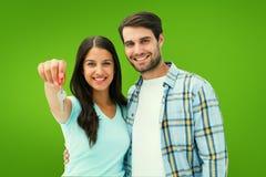 Σύνθετη εικόνα του ευτυχούς νέου ζεύγους που παρουσιάζει κλειδί καινούργιων σπιτιών Στοκ εικόνα με δικαίωμα ελεύθερης χρήσης