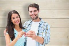 Σύνθετη εικόνα του ευτυχούς νέου ζεύγους που παρουσιάζει κλειδί καινούργιων σπιτιών στοκ εικόνες