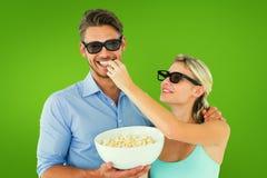 Σύνθετη εικόνα του ευτυχούς νέου ζεύγους που φορά τα τρισδιάστατα γυαλιά που τρώνε popcorn Στοκ Εικόνα