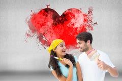 Σύνθετη εικόνα του ευτυχούς νέου ζεύγους που χρωματίζει μαζί και που γελά Στοκ Εικόνα
