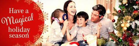 Σύνθετη εικόνα του ευτυχούς οικογενειακού παιχνιδιού με τα δώρα Χριστουγέννων στοκ εικόνες