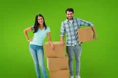 Σύνθετη εικόνα του ελκυστικού νέου ζεύγους με την κίνηση των κιβωτίων Στοκ φωτογραφία με δικαίωμα ελεύθερης χρήσης