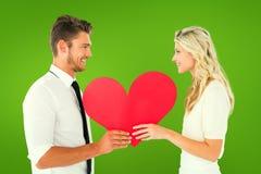 Σύνθετη εικόνα του ελκυστικού νέου ζεύγους που κρατά την κόκκινη καρδιά Στοκ Εικόνες