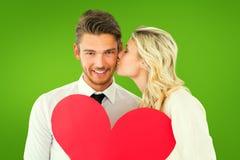 Σύνθετη εικόνα του ελκυστικού νέου ζεύγους που κρατά την κόκκινη καρδιά Στοκ φωτογραφία με δικαίωμα ελεύθερης χρήσης