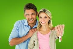 Σύνθετη εικόνα του ελκυστικού νέου ζεύγους που παρουσιάζει κλειδί καινούργιων σπιτιών Στοκ Φωτογραφίες