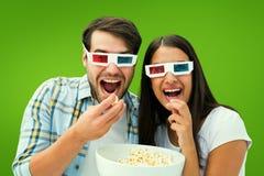 Σύνθετη εικόνα του ελκυστικού νέου ζεύγους που προσέχει έναν τρισδιάστατο κινηματογράφο Στοκ φωτογραφία με δικαίωμα ελεύθερης χρήσης