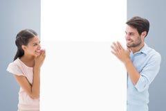 Σύνθετη εικόνα του ελκυστικού νέου ζεύγους που χαμογελά και που κρατά την αφίσα Στοκ Εικόνα