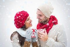 Σύνθετη εικόνα του ελκυστικού νέου ζεύγους στα θερμά ενδύματα που κρατά τις κούπες Στοκ εικόνα με δικαίωμα ελεύθερης χρήσης