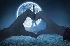 Σύνθετη εικόνα του ζεύγους που κάνει τη μορφή καρδιών με τα χέρια Στοκ Εικόνα