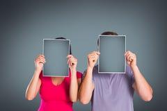 Σύνθετη εικόνα του ζεύγους που καλύπτει τα πρόσωπα με το έγγραφο Στοκ φωτογραφία με δικαίωμα ελεύθερης χρήσης