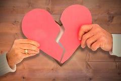 Σύνθετη εικόνα του ζεύγους που κρατά μια σπασμένη καρδιά εγγράφου Στοκ φωτογραφία με δικαίωμα ελεύθερης χρήσης
