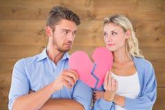 Σύνθετη εικόνα του ζεύγους που κρατά δύο μισά της σπασμένης καρδιάς στοκ εικόνα