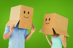 Σύνθετη εικόνα του ζεύγους που φορά emoticon τα κιβώτια προσώπου στα κεφάλια τους Στοκ εικόνα με δικαίωμα ελεύθερης χρήσης