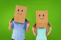Σύνθετη εικόνα του ζεύγους που φορά emoticon τα κιβώτια προσώπου στα κεφάλια τους Στοκ φωτογραφία με δικαίωμα ελεύθερης χρήσης