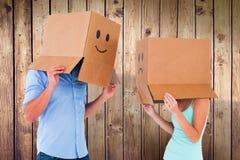 Σύνθετη εικόνα του ζεύγους που φορά emoticon τα κιβώτια προσώπου στα κεφάλια τους Στοκ Φωτογραφίες
