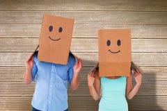 Σύνθετη εικόνα του ζεύγους που φορά emoticon τα κιβώτια προσώπου στα κεφάλια τους Στοκ φωτογραφίες με δικαίωμα ελεύθερης χρήσης