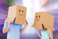 Σύνθετη εικόνα του ζεύγους που φορά emoticon τα κιβώτια προσώπου στα κεφάλια τους Στοκ Φωτογραφία