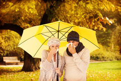 Σύνθετη εικόνα του ζεύγους που φτερνίζεται στον ιστό στεμένος κάτω από την ομπρέλα Στοκ εικόνες με δικαίωμα ελεύθερης χρήσης