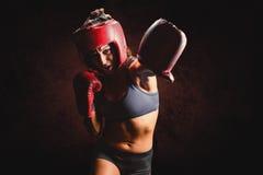 Σύνθετη εικόνα του θηλυκού μπόξερ με τα γάντια και punching καλυμμάτων Στοκ εικόνα με δικαίωμα ελεύθερης χρήσης