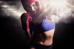 Σύνθετη εικόνα του θηλυκού μπόξερ με τα γάντια και punching καλυμμάτων Στοκ φωτογραφία με δικαίωμα ελεύθερης χρήσης