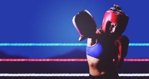 Σύνθετη εικόνα του θηλυκού μπόξερ με τα γάντια και punching καλυμμάτων Στοκ Εικόνες