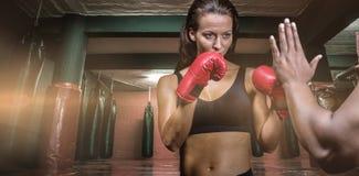 Σύνθετη εικόνα του θηλυκού μπόξερ με τη θέση πάλης ενάντια στο χέρι εκπαιδευτών Στοκ εικόνα με δικαίωμα ελεύθερης χρήσης