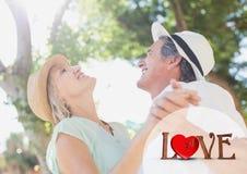 Σύνθετη εικόνα του κειμένου και του ζεύγους αγάπης που χορεύουν μια ηλιόλουστη ημέρα Στοκ εικόνα με δικαίωμα ελεύθερης χρήσης
