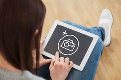 Σύνθετη εικόνα του κοριτσιού που χρησιμοποιεί μια συνεδρίαση PC ταμπλετών στο πάτωμα Στοκ Φωτογραφίες