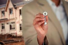 Σύνθετη εικόνα του μέσου τμήματος του ανώτατου στελέχους επιχείρησης που παρουσιάζει κλειδί σπιτιών Στοκ Εικόνες