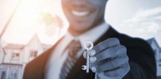Σύνθετη εικόνα του μέσου τμήματος του επιχειρηματία που παρουσιάζει κλειδί καινούργιων σπιτιών Στοκ Φωτογραφία