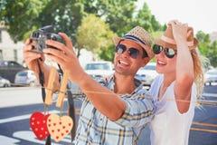 Σύνθετη εικόνα του νέου ζεύγους ισχίων που παίρνει ένα selfie Στοκ Εικόνα