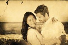 Σύνθετη εικόνα του νέου ζεύγους που αγκαλιάζει και που θέτει στην παραλία Στοκ Εικόνες