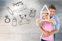 Σύνθετη εικόνα του νέου ζεύγους που αγκαλιάζει και που κρατά την περίληψη σπιτιών στοκ εικόνες