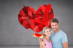 Σύνθετη εικόνα του νέου ζεύγους που αγκαλιάζει και που κρατά τον κύλινδρο χρωμάτων Στοκ Φωτογραφία