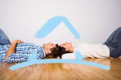 Σύνθετη εικόνα του νέου ζεύγους που βρίσκεται στο χαμόγελο πατωμάτων Στοκ Εικόνες