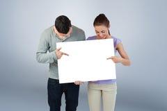 Σύνθετη εικόνα του νέου ζεύγους που δείχνει στο έμβλημα κρατούν Στοκ Φωτογραφίες