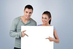 Σύνθετη εικόνα του νέου ζεύγους που δείχνει στο έμβλημα μπροστά από τους Στοκ Εικόνες