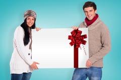 Σύνθετη εικόνα του νέου ζεύγους που κρατά μια αφίσα Στοκ εικόνες με δικαίωμα ελεύθερης χρήσης