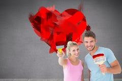 Σύνθετη εικόνα του νέου ζεύγους που χαμογελά και που κρατά τα πινέλα Στοκ εικόνα με δικαίωμα ελεύθερης χρήσης