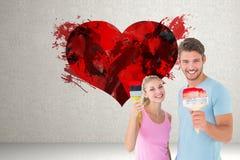 Σύνθετη εικόνα του νέου ζεύγους που χαμογελά και που κρατά τα πινέλα Στοκ Εικόνες