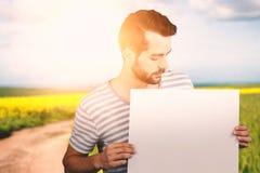 Σύνθετη εικόνα του νεαρού άνδρα που εξετάζει το κενό χαρτόνι Στοκ φωτογραφία με δικαίωμα ελεύθερης χρήσης
